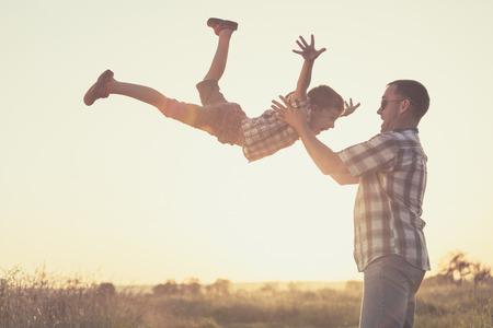 아버지와 일몰 시간에 공원에서 노는 아들. 사람들은 필드에 재미. 친화적 인 가족의 여름 휴가의 개념입니다. 스톡 콘텐츠 - 64894022