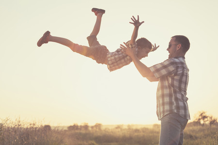 Father and son playing in the park at the sunset time. People having fun on the field. Concept of friendly family and of summer vacation. Reklamní fotografie