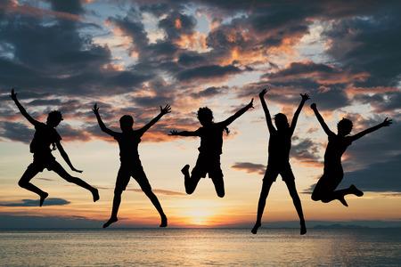 幸せな女の子は、日没時にビーチでジャンプします。人々 は屋外の楽しい時を過します。チームの成功のコンセプトです。