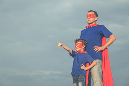 Father and son playing superhero at the day time. People having fun outdoors. Concept of friendly family. 版權商用圖片 - 64441379