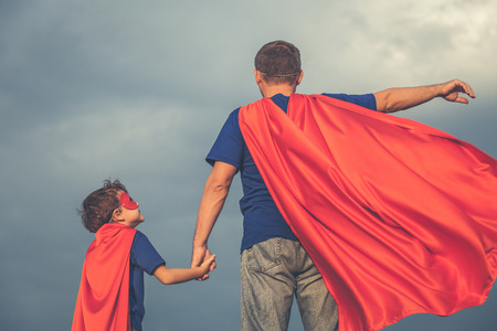 Père et fils jouant super-héros au moment de la journée. Les gens amuser à l'extérieur. Concept de famille sympathique. Banque d'images