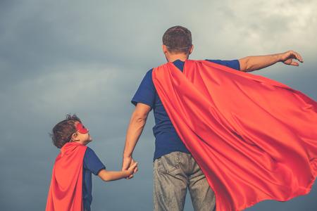 Vater und Sohn, die zur Tageszeit Superhelden spielen. Leute, die Spaß draußen haben. Konzept der freundlichen Familie. Standard-Bild