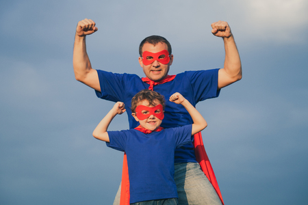 Father and son playing superhero at the day time. People having fun outdoors. Concept of friendly family. Zdjęcie Seryjne - 64441382