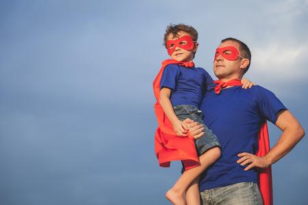 Vater und Sohn spielen Superhelden am Tag Zeit. Menschen Spaß im Freien. Konzept der freundliche Familie. Lizenzfreie Bilder