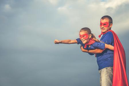 父亲和女儿白天扮演超级英雄。人们在户外享受乐趣。友好家庭的概念。