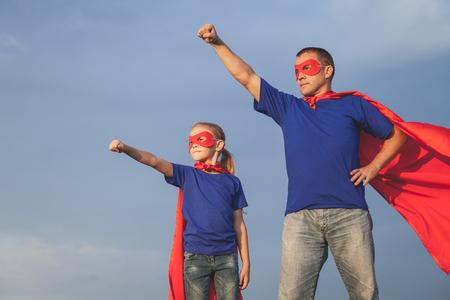 Vader en dochter spelen superheld op de dag de tijd. Mensen met plezier buiten. Concept van vriendelijke familie.