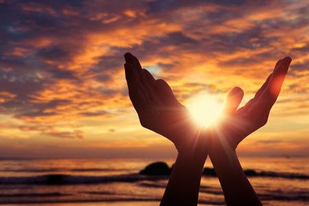 日没時に女性の手のシルエット。生活の概念