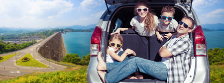 Happy father and children sitting in the car at the sunny day. Concept of friendly family on vacation. Standard-Bild