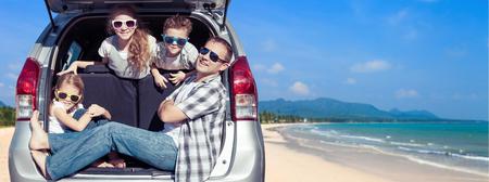 幸せな父と子供たちは晴れた日に車の中で座っています。人々 は屋外の楽しい時を過します。フレンドリーな家族休暇の概念。