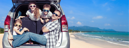 Happy father and children sitting in the car at the sunny day. People having fun outdoors. Concept of friendly family on vacation. Standard-Bild