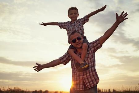 Vater und Sohn im Park bei Sonnenuntergang Zeit zu spielen. Menschen Spaß auf dem Feld. Konzept der freundlichen Familie und der Sommerferien.