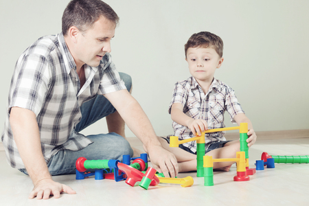 baby playing: Daddy with little boy playing with toy on the floor at the day time. Concept of friendly family.