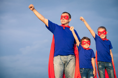 Father and children playing superhero at the day time. People having fun outdoors. Concept of friendly family. Banco de Imagens - 69478069