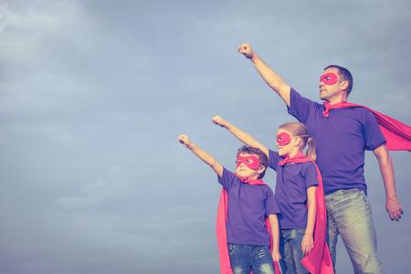 Ojciec i dzieci bawiące superbohatera w czasie dnia. Ludzie zabawy na wolnym powietrzu. Koncepcja przyjazny rodzinie. Zdjęcie Seryjne