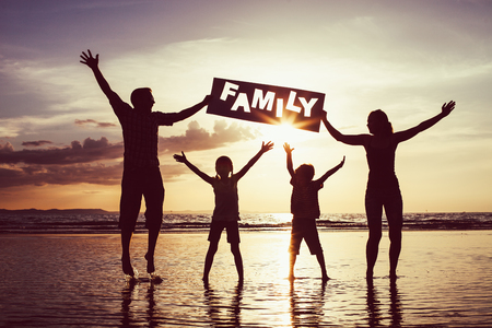 """Happy family jumping on the beach at the sunset time. Parents hold in the hands inscription """"Family"""". Concept of happy family."""