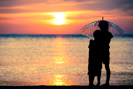silueta niño: hermanas tristes y hermano de pie en la playa en el momento de la puesta del sol