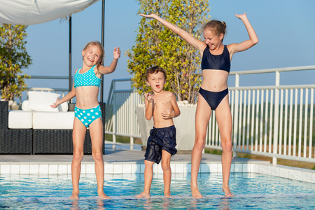 Tre bambini felici che giocano vicino alla piscina, al momento giorno. La gente divertirsi all'aria aperta. Concetto di amichevole vacanza in famiglia e in estate. Archivio Fotografico - 68526340