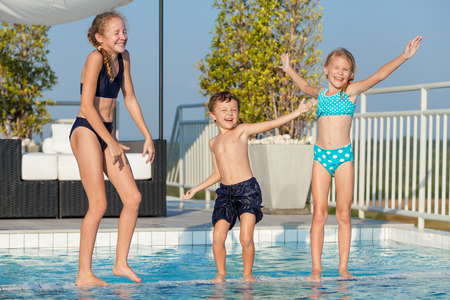 Three happy children playing near swimming pool at the day time.  People having fun outdoors. Concept of friendly family and  summer vacation.