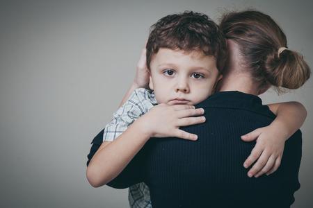 triste hijo abraza a su madre en casa. Concepto de familia pareja está en el dolor. Foto de archivo