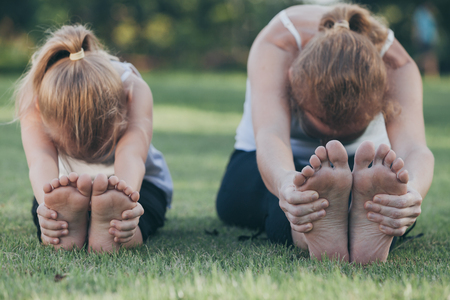 Mother and daughter doing yoga exercises on grass in the park at the day time. People having fun outdoors. Concept of friendly family and of summer vacation.