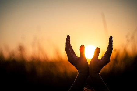 pray: silhouette of female hands during sunset. Concept of life. Stock Photo