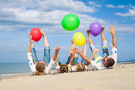 一日の時間でビーチに風船で遊んで幸せな家族。 人々 ビーチで楽しんで。フレンドリーな家族の夏休みの概念。