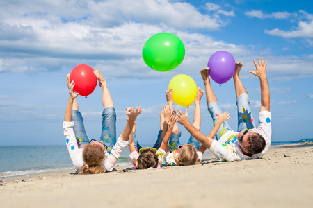 słońce: Szczęśliwa rodzina bawi się z balonów na plaży w czasie dnia. Ludzie bawią się na plaży. Koncepcja przyjaznej rodziny i letniego wypoczynku. Zdjęcie Seryjne