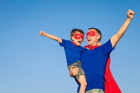 дети: Отец и сын играет супергероя в дневное время. Люди с удовольствием на открытом воздухе. Концепция дружной семьи.