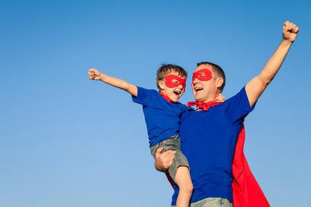 hombre rojo: Padre e hijo jugando superhéroe en el tiempo del día. Las personas que se divierten al aire libre. Concepto de la familia.