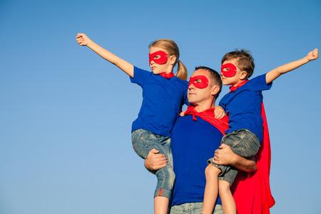 白天父亲和孩子们扮演超级英雄。人们在户外享受乐趣。友好家庭的概念。