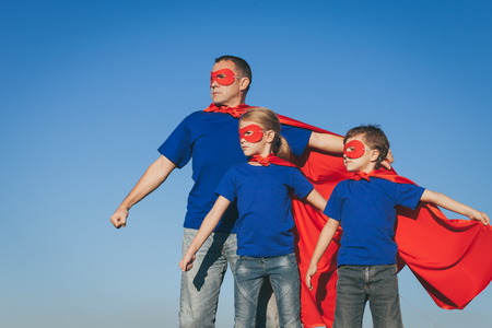 day dream: Father and children playing superhero at the day time. People having fun outdoors. Concept of friendly family.