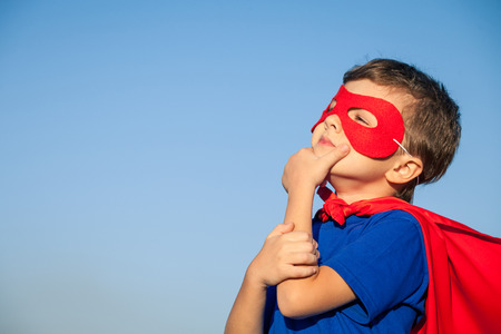 Happy little child playing superhero. Kid having fun outdoors. Concept of boy power. Stock Photo