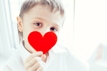 little one: One little boy standing near a window. Concept of happy Valentine day. Stock Photo