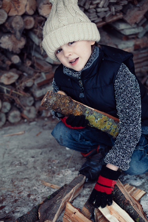 little one: One little boy chopping firewood in the front yard at the day time. Kid having fun outdoors. Concept happy lifestyle.