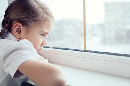 una niña triste sentada cerca de la ventana en el momento del día. Concepto de dolor