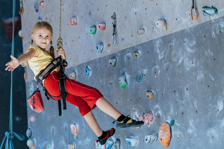 little girl climbing a rock wall indoor. Concept of sport life.