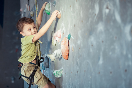 little boy climbing a rock wall indoor. Concept of sport life.