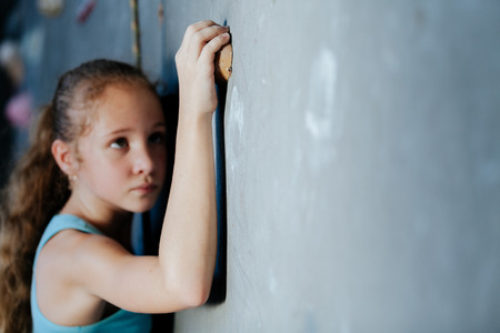 one teenager: One teenager climbing a rock wall indoor. Concept of sport life. Stock Photo