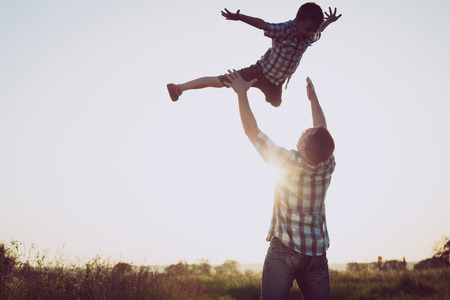 父と息子の日没の時に公園で遊んで。人々 は、フィールド上で楽しんで。フレンドリーな家族の夏休みの概念。 写真素材