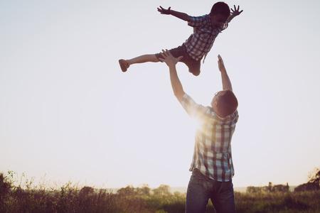 아버지와 일몰 시간에 공원에서 노는 아들. 사람들은 필드에 재미. 친화적 인 가족의 여름 휴가의 개념입니다.
