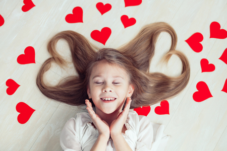 little one: One little girl lying on the floor. Concept of happy Valentine day.