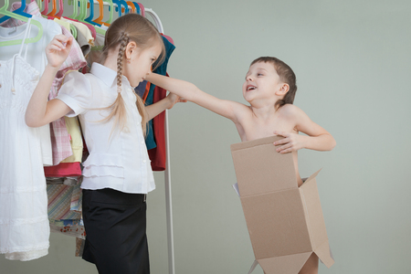 shirt hanger: Two little children standing near a hanger with clothes at home at the day time. Kids having fun indoor.