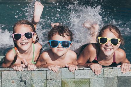 niños felices: Tres niños felices jugando en la piscina en el tiempo del día. Cabrito que se divierten al aire libre. Concepto de la familia.