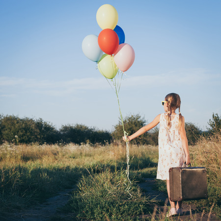 fun day: Happy little girl playing on road at the day time. She standing in the field and holding in hands suitcase and balloons. Kid having fun on the nature. Concept of happiness.