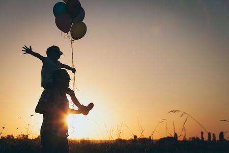 父と息子の日没の時に公園で風船で遊ぶ。人々 は、フィールド上で楽しんで。フレンドリーな家族の夏休みの概念。
