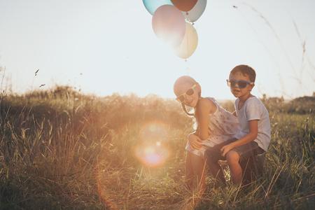 Gelukkige kleine kinderen die op weg in de zonsondergangtijd spelen. Ze zitten op de koffer in het park en houden de ballonnen in de hand. Kinderen hebben plezier in de natuur. Concept van geluk.