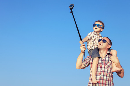 Father and son playing in the park  at the day time. Concept of friendly family. Picture made on the background of blue sky. Stock Photo