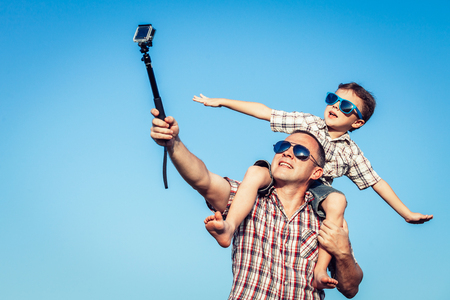 Father and son playing in the park  at the day time. Concept of friendly family. Picture made on the background of blue sky. Reklamní fotografie