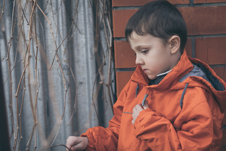 dreary: Portrait of sad little boy outdoors at the day time. Concept of dreary spring. Stock Photo
