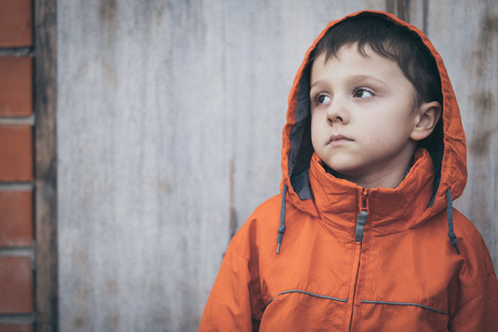 Portrait of sad little boy outdoors at the day time. Concept of dreary spring. Stock Photo
